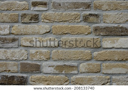 Weathered yellow brick wall with concrete seam. - stock photo