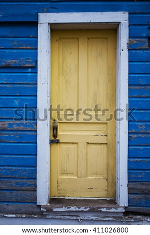 Weathered yellow door inset in faded and peeling exterior blue wood board wall