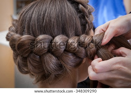 weaving braids brunette in a hairdressing salon - stock photo