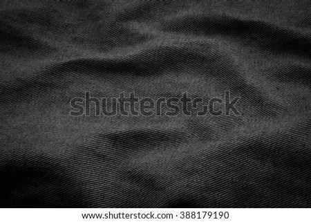 weaving dark black jeans fabric texture background with vignette.rough/creased denim fabric textures in vintage color.wrinkle fabric burlap backdrop concept.garment textile wallpaper:square frame  - stock photo