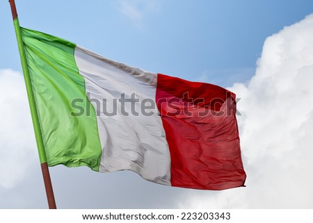 Weaving Italian three colors flag of Italy on the blue sky background