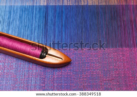 Weaving shuttle with thread on the blue warp - stock photo