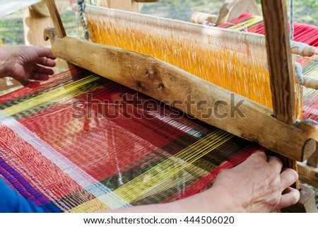 Weaving the threads on old wooden loom - stock photo
