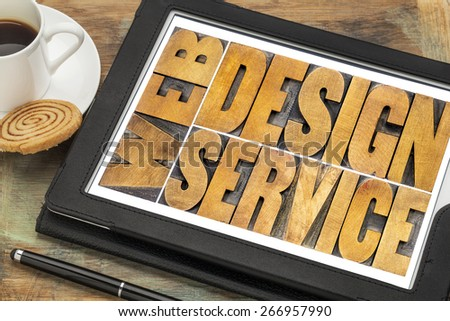 web design service word abstract - isolated text in letterpress wood type on a digital tablet with a cup of coffee - stock photo
