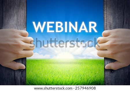 Webinar. Hand opening an old wooden door and found Webinar word floating over green field and bright blue Sky Sunrise. - stock photo