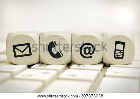 Website and Internet contact us page concept with black icons on cubes on a keyboard - stock photo