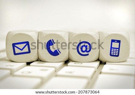 Website and Internet contact us page concept with blue icons on cubes on a keyboard - stock photo