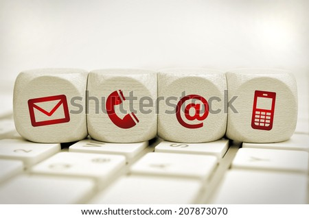 Website and Internet contact us page concept with red icons on cubes on a keyboard - stock photo