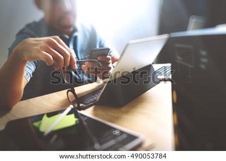 eyeglasses designer jgev  Website designer holding eyeglasses and working digital tablet dock  keyboard and computer laptop with smart phone