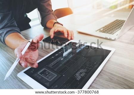 Website designer working digital tablet and computer laptop and digital design diagram on wooden desk as concept - stock photo
