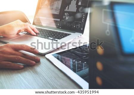 Website designer working digital tablet and computer laptop with digital tablet and digital design diagram on wooden desk and compact server - stock photo