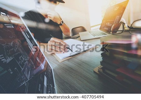 Website designer working digital tablet and computer laptop with smart phone and digital design diagram and stack of books on wooden desk as concept - stock photo