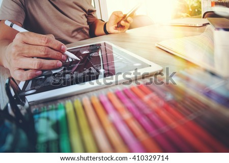 Website designer working digital tablet and computer laptop with smart phone and graphics design diagram on wooden desk as concept - stock photo