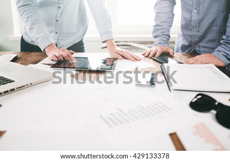 Website developers working using  laptop at the office on wooden table. Film effect