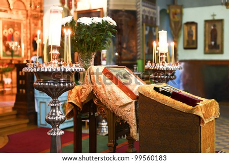 Wedding accessories and interior in Saint Trinity Orthodox Convent including two candlesticks with many candles, flowers, icons and Holy Bible. Wonderful church in Riga, Latvia