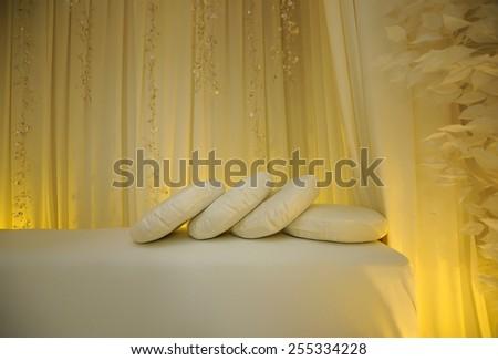Wedding accessories. Beautiful wedding pillows on a wedding bench. - stock photo