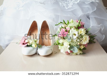 Wedding accessories: shoes, boutonniere and bride's bouquet - stock photo