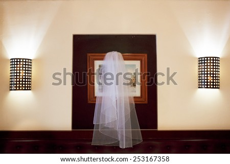 Wedding accessories. Veil hangs over the bed between two lamps. - stock photo