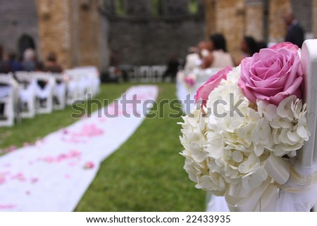 Wedding aisle and bouquet with unidentifiable guest - stock photo