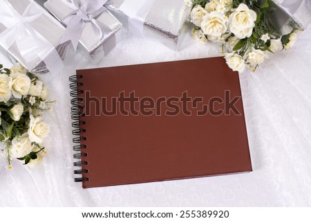 Wedding album or writing book laid on bridal lace with several silver wedding gifts and white rose bouquets.  Wedding list, record or photo album.  Space for copy. - stock photo