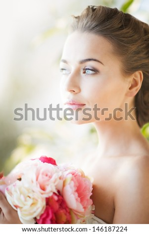 wedding and beauty concept - young woman with bouquet of flowers