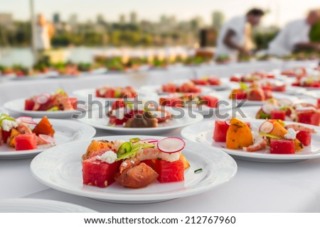 Wedding and event food preparation. Elegantly decorated by chef a salad with shrimp, water melon, reddish and fruits on the picnic table outdoors with an ocean view and city as a background  - stock photo
