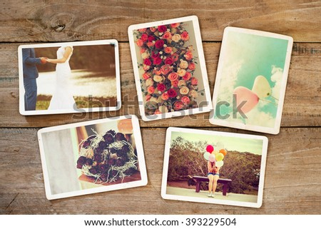 Wedding and honeymoon instant photo album on wood table. paper photo of film camera - vintage and retro style - stock photo