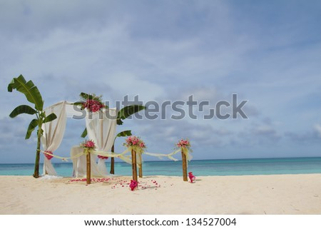 wedding arch and set up with flowers on tropical beach - stock photo