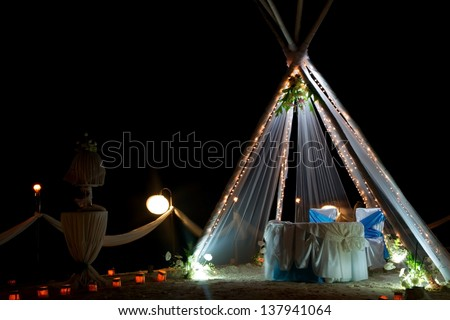 wedding arch and set up with flowers on tropical beach at night - stock photo