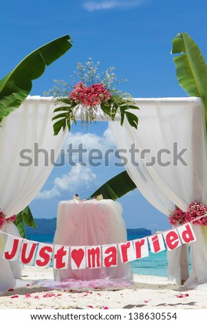 wedding arch and set up with flowers on tropical beach under palm trees - stock photo
