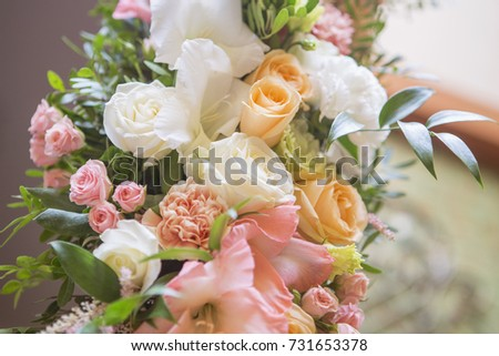 Wedding arch decor full of rose and eustoma flowers, candles and peach colored fabric. Luxury rich restaurant interior. Indoor. Copy space