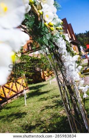 wedding arch decorated outdoors orchid flowers - stock photo