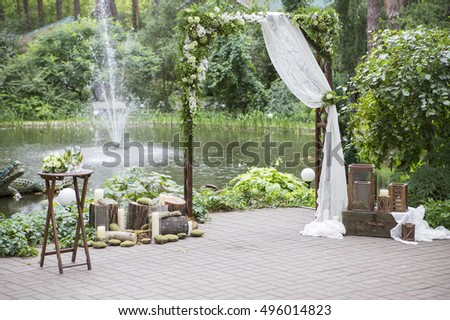 Wedding arch decorated with eustoma roses flowers on a wedding ceremony. Soft day light, outdoor in garden