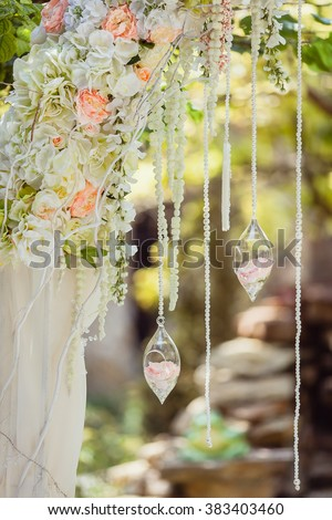 Wedding arch decorated with flowers and glass hanging vases - stock photo