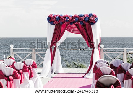 Wedding arch of different flowers on a background of the sea - stock photo