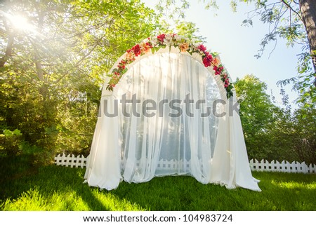 Wedding Arch with flowers on the grass - stock photo