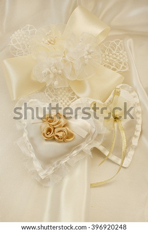 Wedding background with large flower and handmade hearts. Romantic beige background for congratulations. Ribbons, beads and folds in the fabric. - stock photo