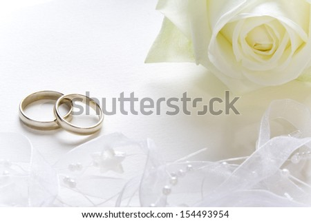 Wedding background with wedding bands and white rose. - stock photo