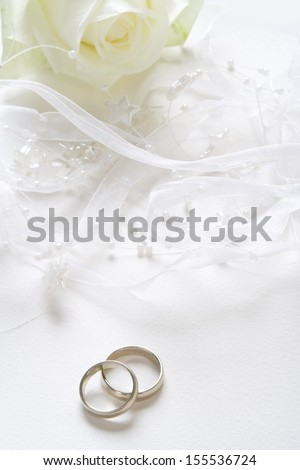 Wedding background with wedding bands and white rose.