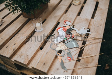Wedding. Banquet. Decor. On a wooden table from the storage of pallets is the composition of pine branches and lay jewelry and accessories in the form of flags and hearts - stock photo