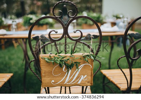 """Wedding. Banquet. Honeymoon chairs with wooden signs """"Mr"""" and """"Mrs"""". Chairs stand on a green lawn in the backyard banquet area - stock photo"""
