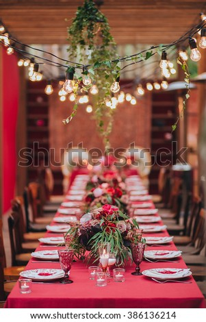 Wedding. Banquet. Marsala. In the forest on a wooden porch is served banquet table with a tablecloth color marsala and vintage chairs. On the table is floral composition and cutlery, glasses, candles