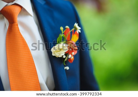 wedding beautiful boutonniere on suit of groom. Man in blue suit, shirt and orange tie.  - stock photo