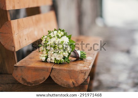 Wedding beautiful bridal bouquet lying on a wooden bench