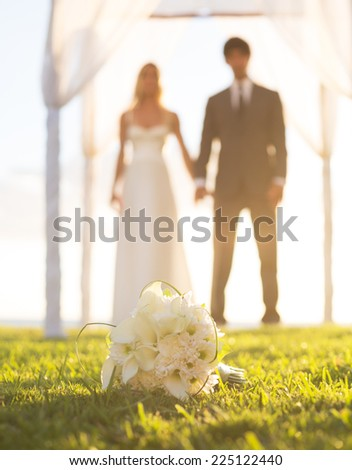 Wedding, Beautiful Bride and Groom Holding Hands. Focus of Bouquet, Shallow Depth of Field - stock photo
