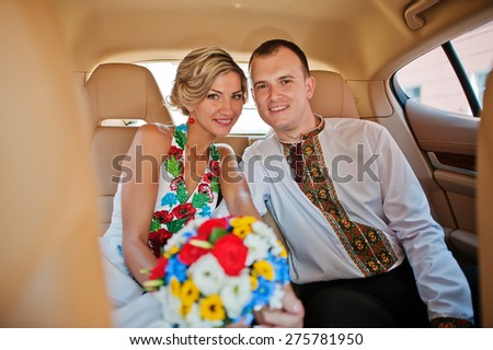 Wedding beautiful couple in traditional dress in exotic supercar - stock photo