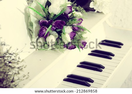 Wedding beautiful flowers on vintage piano - stock photo