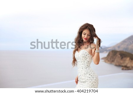 Wedding. Beauty Fashion Elegant bride woman. Brunette model in luxurious fashion white gown posing by infinity swimming pool over sea. outdoor portrait. - stock photo