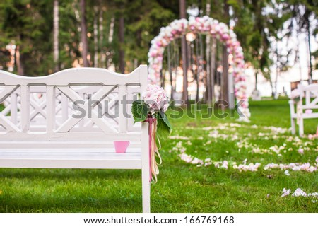 Wedding benches and flower arch for ceremony outdoors - stock photo