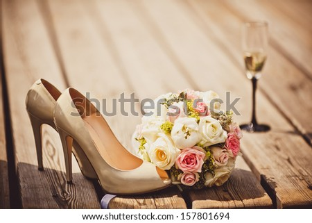 Wedding bouquet and bride shoes - stock photo